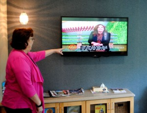 Rhonda Mulder, manager of quality and performance improvement at District One Hosp. shows closed captioning in effect in a waiting room at the Surgery Center (Gunnar Olson/Daily News)